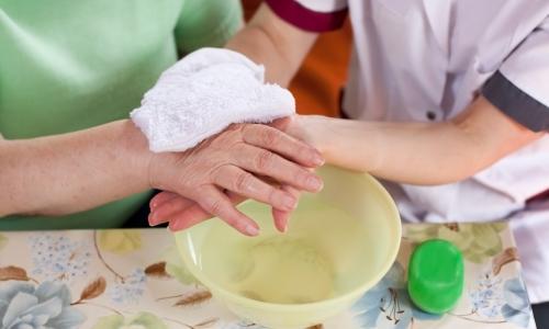 Altenpflegerin wäscht Seniorin die Hände